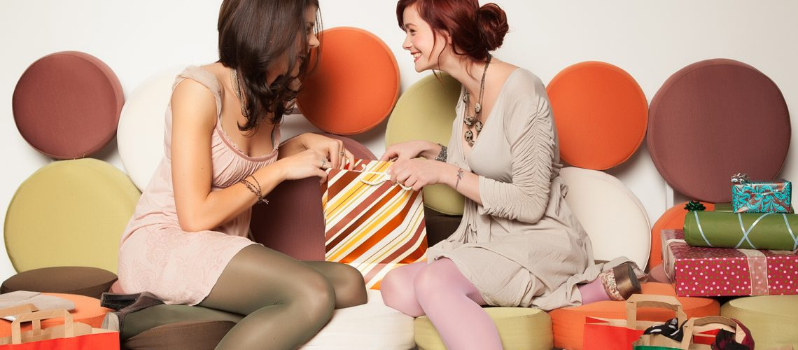 two young beautiful caucasian girls sitting on a colorful sofa with shopping bags and gift boxes around them looking with curiousity in a bag and laughing